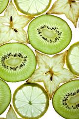 Scheiben von Kiwi, Sternfrucht und Zitrone auf Weiss