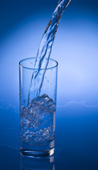 Pouring mineral water stream into a glass