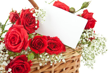 Red roses and blank card in wicker basket