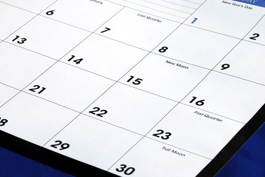 Planning the new month from a calendar isolated on blue