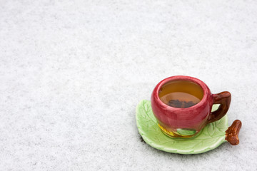 A cup of tea is on the snow