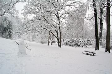 Bonhomme de neige et banc dans un jardin enneigé