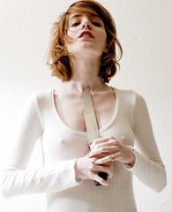 jeune femme en robe blanche tient un couteau contre son cou