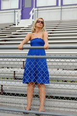 Cheerful blonde in blue dress posing at an outdoor stadium