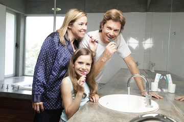 Girl brushing teeth with her parents