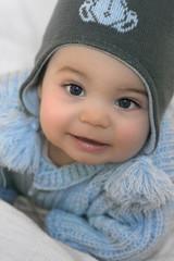 Bébé souriant avec bonnet et manteau d'hiver