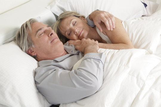 Happy older couple sleeping