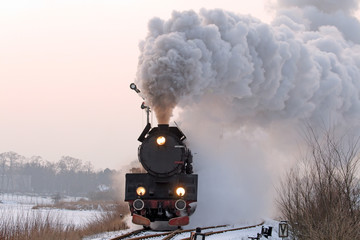 Retro steam train starting from the station during wintertime