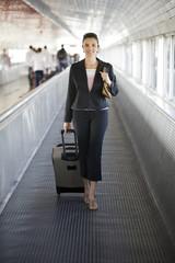 Sexy Frau am Flughafen mit Koffer lächelnd