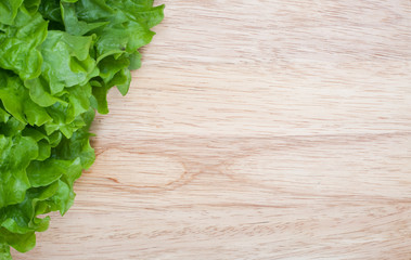 Green lettuce on wooden board with space for text
