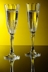 Two glasses of champagne on yellow background.