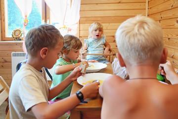 Children having dinner behind table