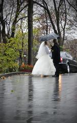 Bride and groom standing under an umbrella