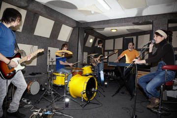 rock band. singer, guitarists, keyboarder and drummer in studio.