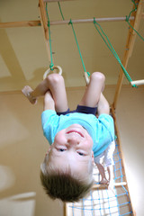 boy hanging on gymnastic rings