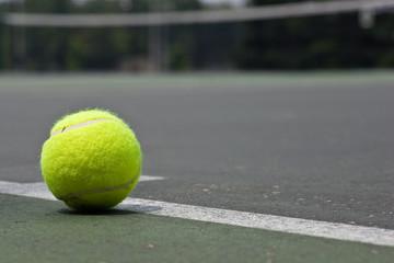 Closeup of tennis ball on base line