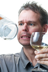 Man holding wine glass and empty bottle with concern