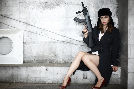 A young and stylish woman holding an assault rifle