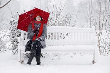 Frau im Schee auf einer Parkbank