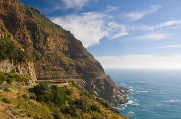 A winding road hugs the rugged coastline of South Africa