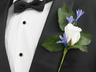 Man Wearing A Suit With A White Rose Corsage