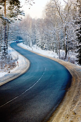Winding road in winter forest