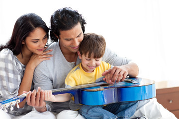 Happy little boy playing guitar with his parents