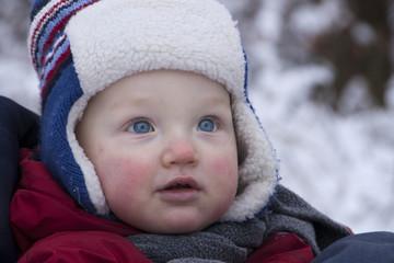 kleiner Junge mit dicker Mütze im frostigen Winterwald