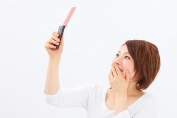 携帯電話を見て驚く女性