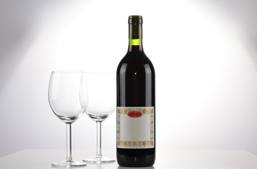 A bottle of wine with blank label and two emtpy wine glasses