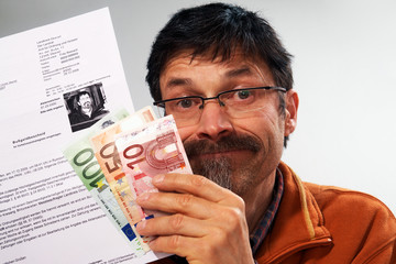 man holding a speed ticket fine and paper money