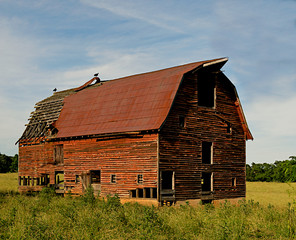 Abandoned old barn surrounded by beautiful blue sky.