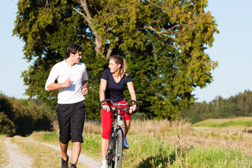 Sport-Paar joggt und fährt Fahrrad