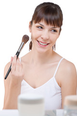 Body care: Young woman applying powder with brush