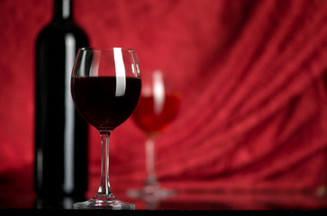 The big glass of red wine and bottle on a red background