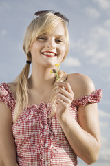 Young woman playing with flower