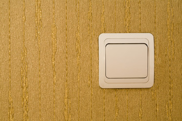 Light switch on a wall with wallpaper of gold color