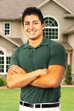Young man with arms crossed in front of a house portrait