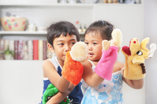 Asian sibling playing hand puppet