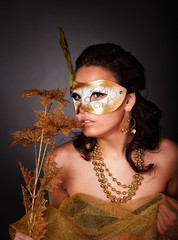 Young woman with mask on grey background.