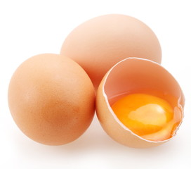 With brown eggs on a white background. One egg is broken.