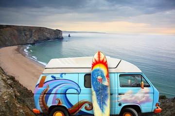 Van and surf board at a beach