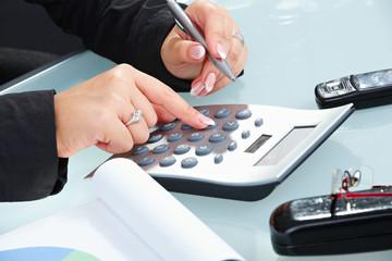 Female hands using calculator