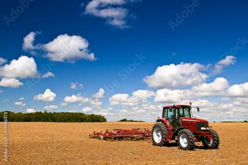 Wall mural Tractor in plowed field