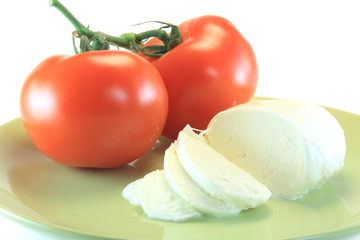 slice of mozzarella and tomato in green plate isolated on white