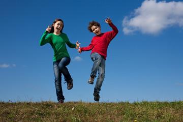 Kids jumping, running against blue sky