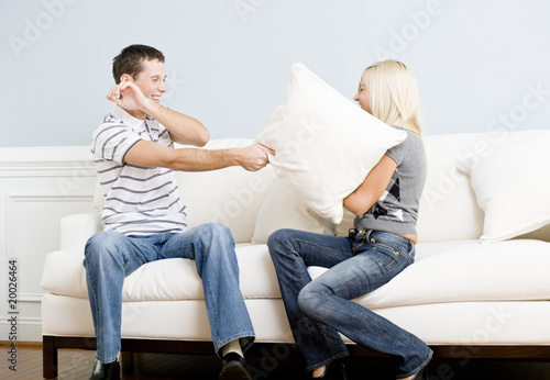 Young Couple Having A Pillow Fight On Sofa Stock Photo And Royalty