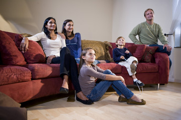 Interracial family together on living room couch watching TV