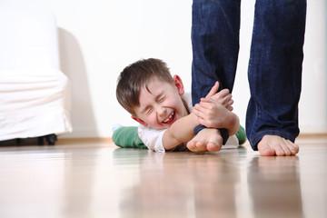 Kind weint und hält sich am Bein der Mutter fest schreit