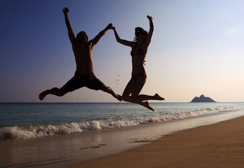 silhouette of couple jumping in the air at a hawaii beach